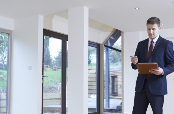Estate Agent Looking Around Vacant Property For Valuation